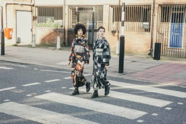 Two people wearing kimonos crossing the road at a zebra crossing