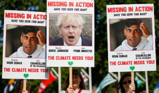 Protesters hold 'Missing in Action' style placards of Prime Minister Boris Johnson and Chancellor Rishi Sunak with the phrase 'The climate needs you!'