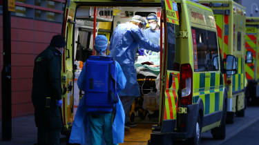 A patient is transported out of an ambulance by medics wearing PPE at the Royal London Hospital.