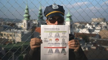 An Austrian policeman holds up a pamphlet setting out the new restrictions