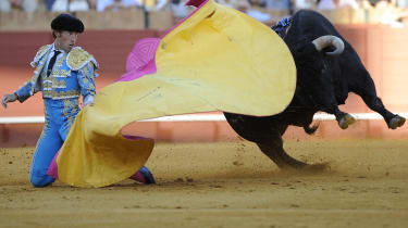 A Spanish matador performs a pass on a bull at the Maestranza Bullring