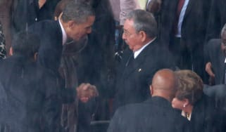 US President Barack Obama shakes hands with Cuban President Raul Castro in South Africa in 2013