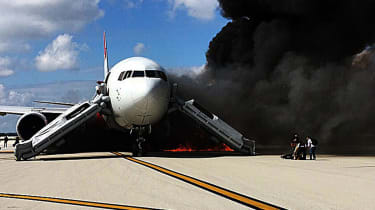 Passengers evacuate from a plane on fire at Fort Lauderdale airport,