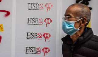Man walks in front of vandalised HSBC store in Hong Kong