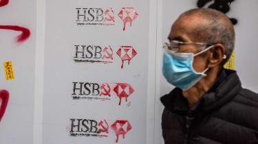 Man walks in front of vandalised HSBC store in Hong Kong