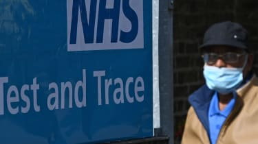 A man wearing a face mask passes a sign for the NHS test-and-trace service.