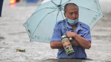 A man wades through flood water in Zhengzhou, Henan province