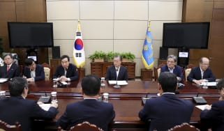 SEOUL, SOUTH KOREA - AUGUST 22: In this handout image provided by South Korean Presidential Blue House, South Korean President Moon Jae-in (C) listens to a report from officials related to th
