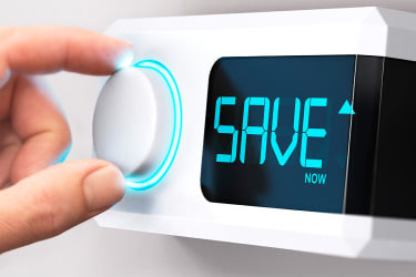 """A hand turning a dial on a thermostat. The digital display reads, """"Save."""""""
