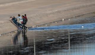 Migrants cross the shallow Rio Grande to gain entry into El Paso, Texas