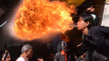 An Indian Hindu devotee performs with fire as he participates in a procession ahead of the Holi festival in Amritsar on March 12, 2014. Holi, the popular Hindu spring festival of colours is o