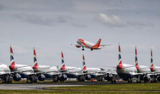 A fleet of British Airway planes sit on the runway at Glasgow Airport as an EasyJet plane takes off.