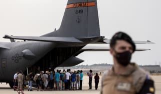 Afghan refugees queue to board a US military plane