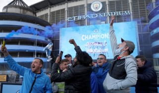 Man City fans celebrate their title win outside the Etihad Stadium