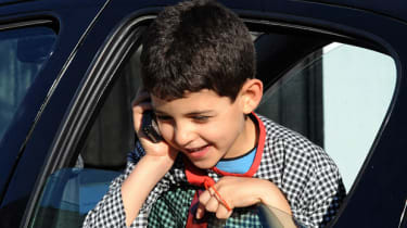 A young boy talks on his mobile phone