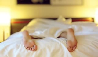 The feet of a person sleeping in a bed