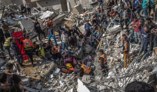 Palestinians search for bodies in the rubble of a bombed building