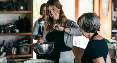 Woman laughing and holding spoon up over mixing bowl