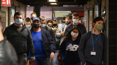 Commuters wear face masks as they pass through Vauxhall underground station.