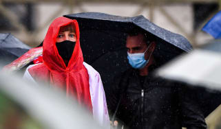 People wearing face masks shelter from the rain.
