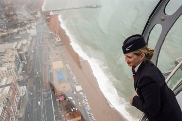 BRIGHTON, ENGLAND - AUGUST 02:A member of British Airways staff looks out of the i360 passenger pod during a press preview on August 2, 2016 in Brighton, England.The British Airways i360, des