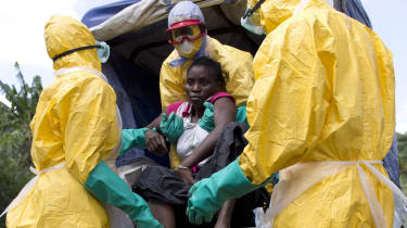 A woman suspected of suffering from Ebola is helped into a van by aid workers.