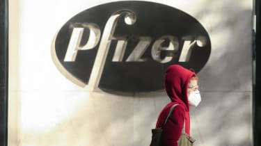 A woman wears a face mask as she walks by the Pfizer world headquarters in New York.