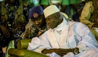 Incumbent Gambian President Yahya Jammeh listens to one of his aides in Banjul on November 29, 2016, during the closing rally of the electoral campaign of the Alliance for Patriotic Reorienta