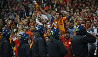 Police watch over Galatasaray supporters during the match between Arsenal and Galatasaray