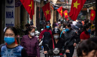 People wear face masks while shopping in Hanoi