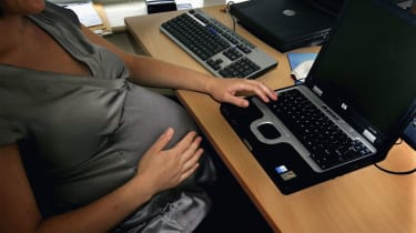 A pregnant woman is seen at the office work station on July 18, 2005 in London, England.