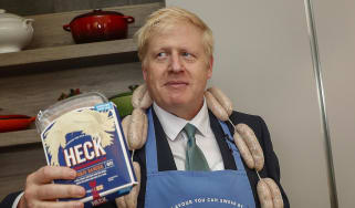 """Boris Johnson poses with a string of sausages called """"Boris Bangers"""" during a visit to Heck Foods."""