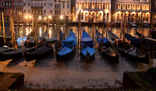 Gondolas are seen tied up in Venice Canal Grande, near Rialto bridge, on January 31, 2018, as exceptionally low tides have drained the lagoon city.The unusually low tides caused a record low