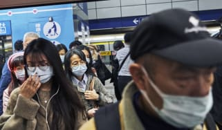 Commuters wearing face masks board a train in Taipei