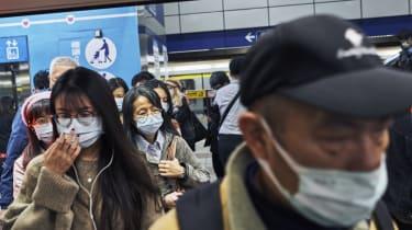 Commuters wearing face masks board a train in Taipei