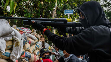 An anti-coup protestor aims an improvised weapon in Yangon, Myanmar