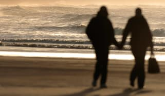 Couple walking on beach in silhouette