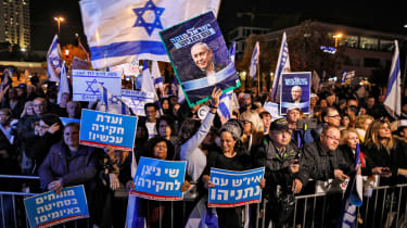 Israelis gather with signs and national flags during a demonstration in support of Prime Minister Benjamin Netanyahu in Jerusalem on December 11, 2019. (Photo by AHMAD GHARABLI / AFP) (Photo