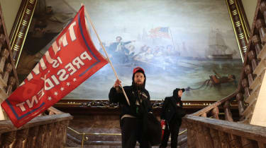 A protester holds a Trump flag inside the US Capitol Building near the Senate Chamber.
