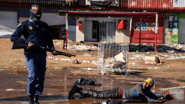A police officer stands over a suspected looter in Soweto, Johannesburg