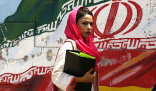 A woman walks in front of a mural painting depicting the Iranian flag, in the capital Tehran