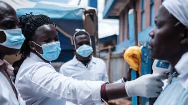 Healthcare workers in Kenya check a patients temperature while dressed in PPE.