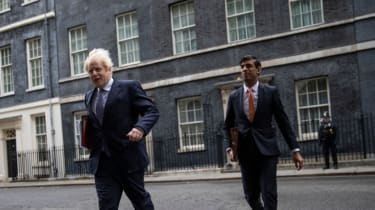 Boris Johnson and Rishi Sunak leave Downing Street to attend a meeting of the cabinet.