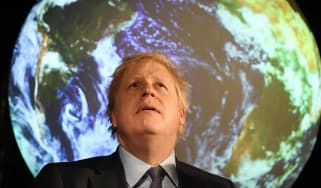 Boris Johnson in front of a projection of Earth