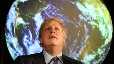 Boris Johnson sits in front of projected earth