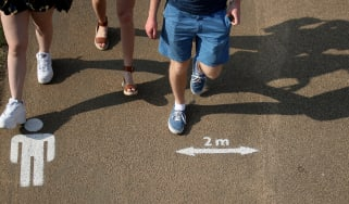 People walk past the social distancing markings on the ground at Queen Elizabeth Olympic Park.