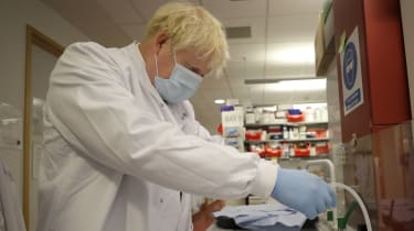 Boris Johnson washes immunological assays during a visit to the Jenner Institute.