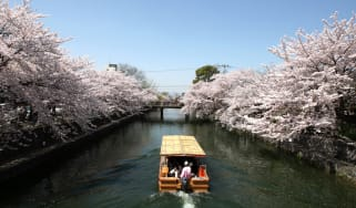 KYOTO, JAPAN - APRIL 05:Tourists travel on a ferry near blooming cherry blossoms on the Okazaki canal on April 5, 2013 in Kyoto, Japan.Cherry blossoms bloom from the end of March to the begin