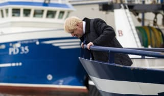 Boris Johnson looks to the water from a fishing trawler during a visit to Peterhead.