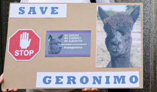 A woman holds a sign that reads 'Save Geronimo'